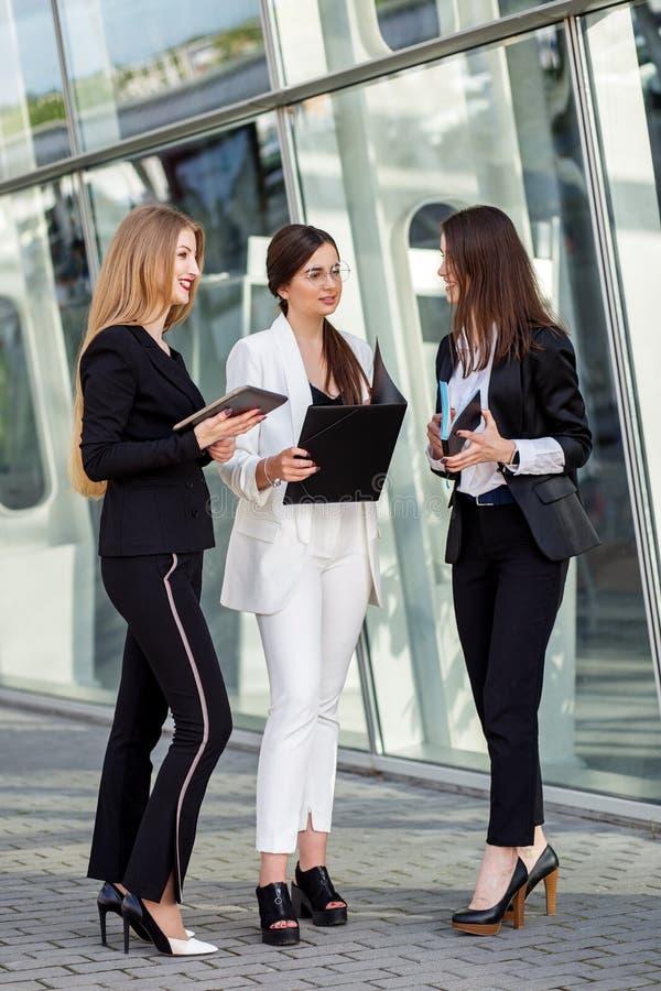 Tre vuxna kvinnor att diskutera uppgiften vertikalt Begrepp för affär, marknadsföring, finans, arbete, kollegor och livsstil royaltyfri foto