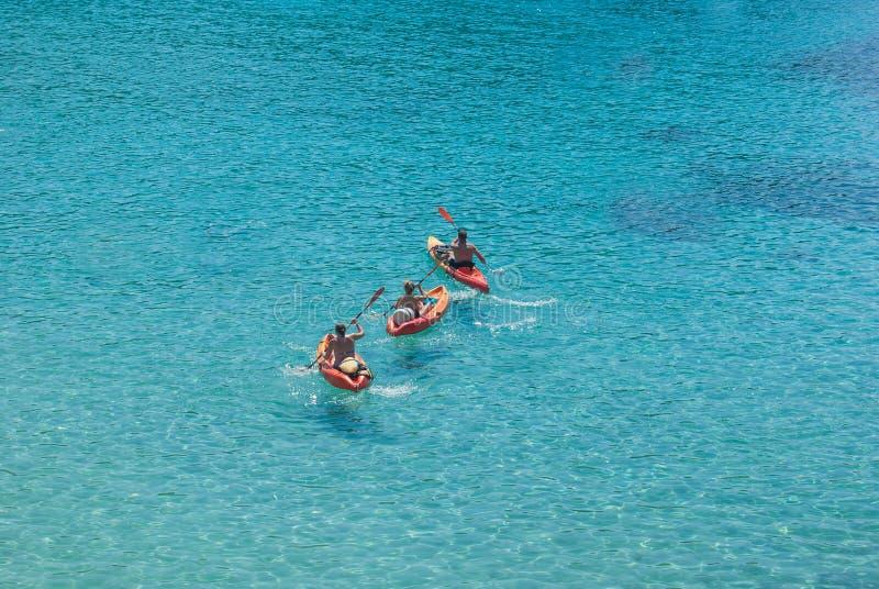 Tre vuxna människor på röda kajaker i havet arkivfoton