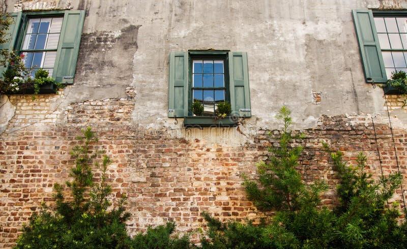 Tre Windows con gli otturatori verdi in vecchio mattone immagine stock