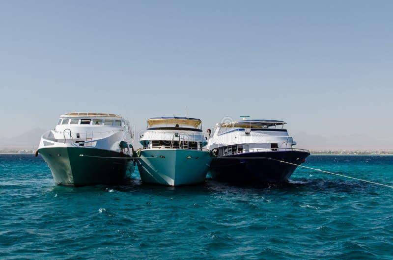 Tre yachter i havet arkivfoton