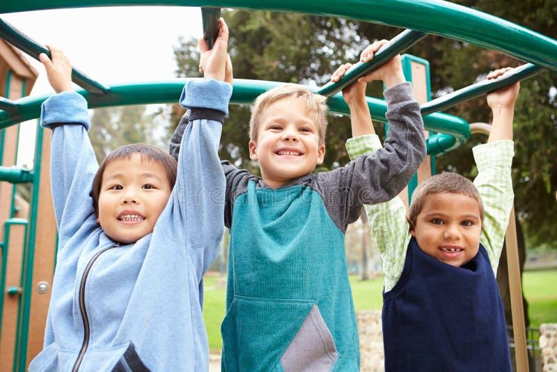 Tre Young Boys på klättringram i lekplats arkivbild