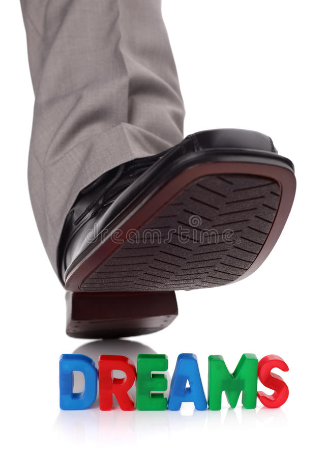 Treading on someones dreams. Businessman foot about to tread on someones dreams concept for broken dreams, bullying or oppression stock photo