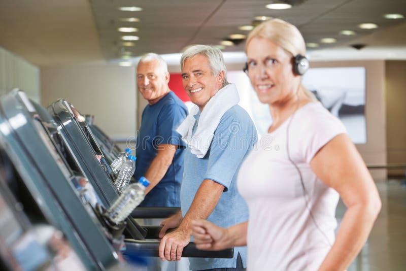 treadmills för gruppidrottshallpensionär arkivbild