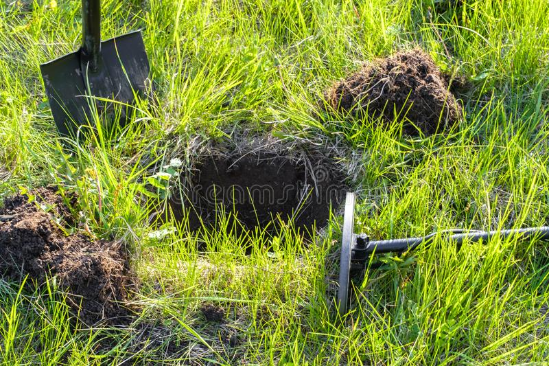 Treasure раскопк, металлоискатель и лопаткоулавливатель на зеленой траве стоковое фото rf