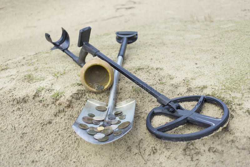 Treasure ancient coins dug out of the ground. Search for treasure using a metal detector and shovel royalty free stock photo