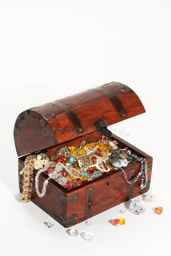 Treasure chest. Filled wiht precious stones and jewelry, isolated, white background stock image