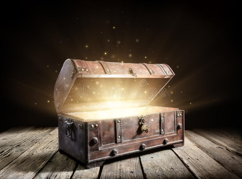 Treasure Chest - Open Ancient Trunk With Glowing Magic Lights stock photo