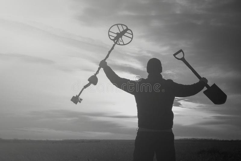 Treasure hunter with a metal detector on a beveled wheat field in search of adventure against the backlight of the sun. Treasure hunter with a metal detector on royalty free stock images
