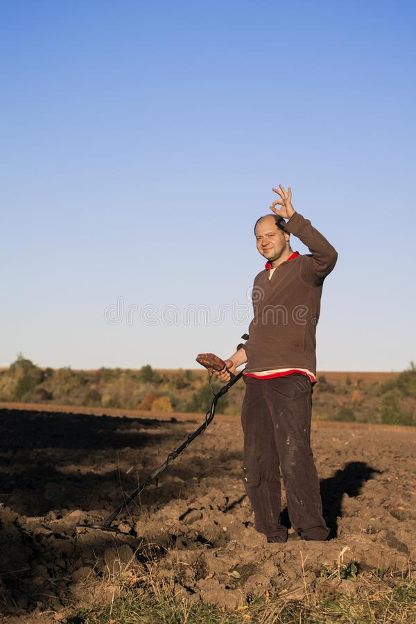 Treasure hunter with a metal detector in his hands and a smile on his face shows a hand sign okay stock photos