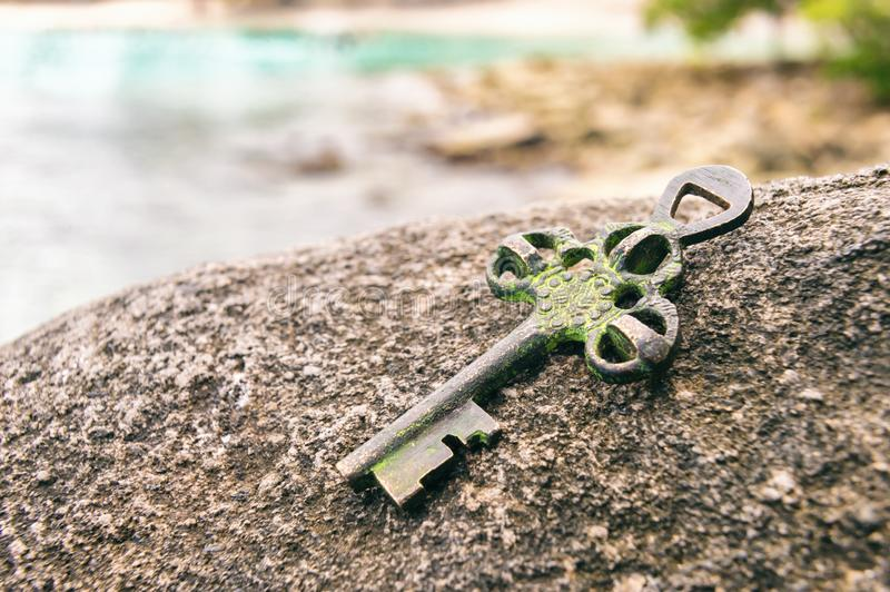 Treasure key lost on rock at the beach royalty free stock photography