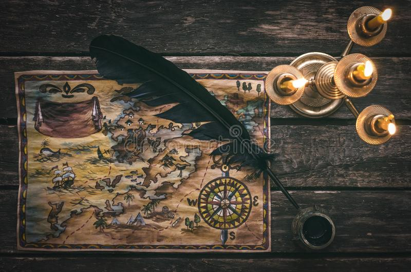 Treasure map. Pirate treasure map, burning candle, feather pen and inkwell on wooden ship table background stock photos