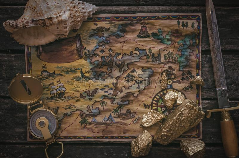 Treasure map. Treasure map, compass and gold nugget on wooden table background stock images