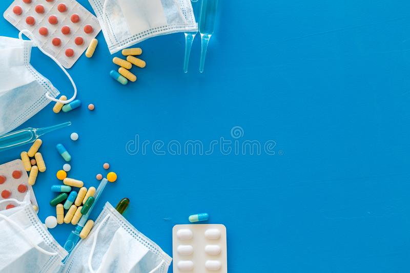 Treat flu and cold concept. Vaccine, mask, pills on blue background top view frame space for text. Treat flu and cold concept. Vaccine, mask, pills on blue stock photos