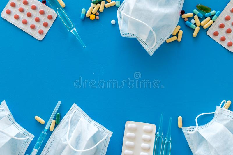 Treat flu and cold concept. Vaccine, mask, pills on blue background top view frame copy space. Treat flu and cold concept. Vaccine, mask, pills on blue stock image