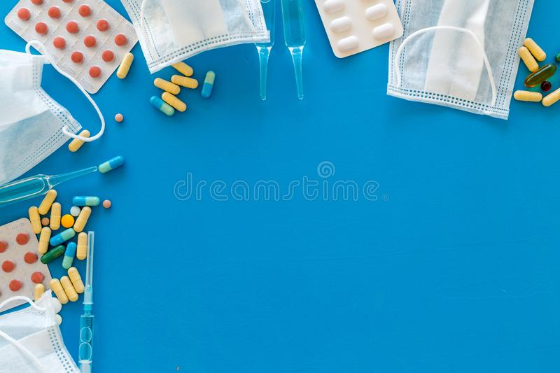 Treat flu and cold concept. Vaccine, mask, pills on blue background top view frame copy space. Treat flu and cold concept. Vaccine, mask, pills on blue royalty free stock image