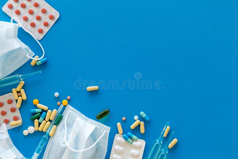 Treat flu and cold concept. Vaccine, mask, pills on blue background top view frame space for text. Treat flu and cold concept. Vaccine, mask, pills on blue royalty free stock image
