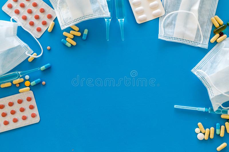 Treat flu and cold concept. Vaccine, mask, pills on blue background top view frame copy space. Treat flu and cold concept. Vaccine, mask, pills on blue stock photo