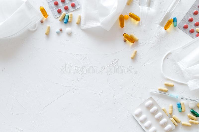 Treat flu and cold concept. Vaccine, mask, pills on white background top view frame copy space. Treat flu and cold concept. Vaccine, mask, pills on white royalty free stock images
