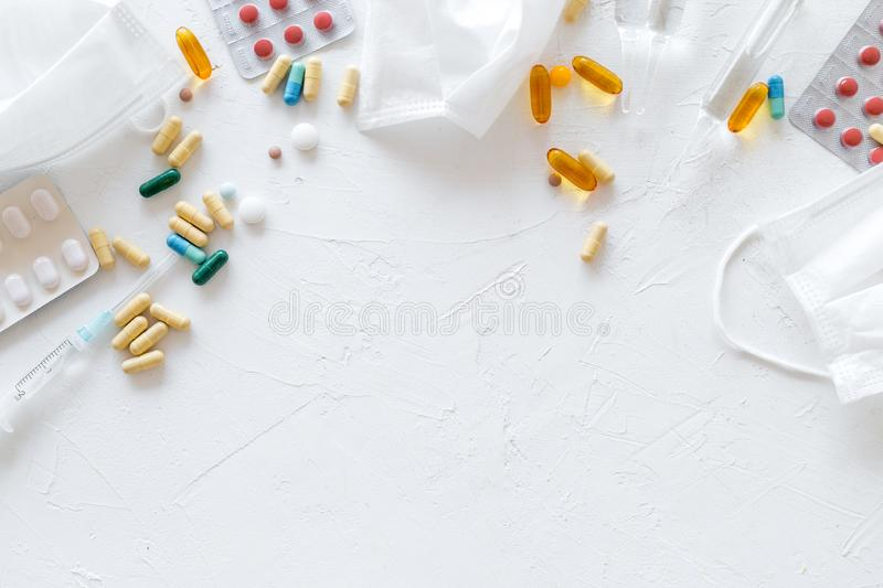 Treat flu and cold concept. Vaccine, mask, pills on white background top view frame copy space. Treat flu and cold concept. Vaccine, mask, pills on white royalty free stock photography