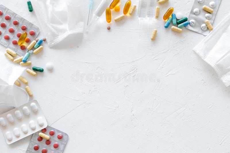 Treat flu and cold concept. Vaccine, mask, pills on white background top view frame copy space. Treat flu and cold concept. Vaccine, mask, pills on white stock photos