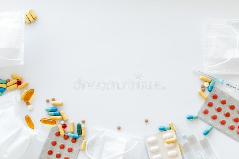 Treat flu and cold concept. Vaccine, mask, pills on white background top view frame copy space. Treat flu and cold concept. Vaccine, mask, pills on white stock images