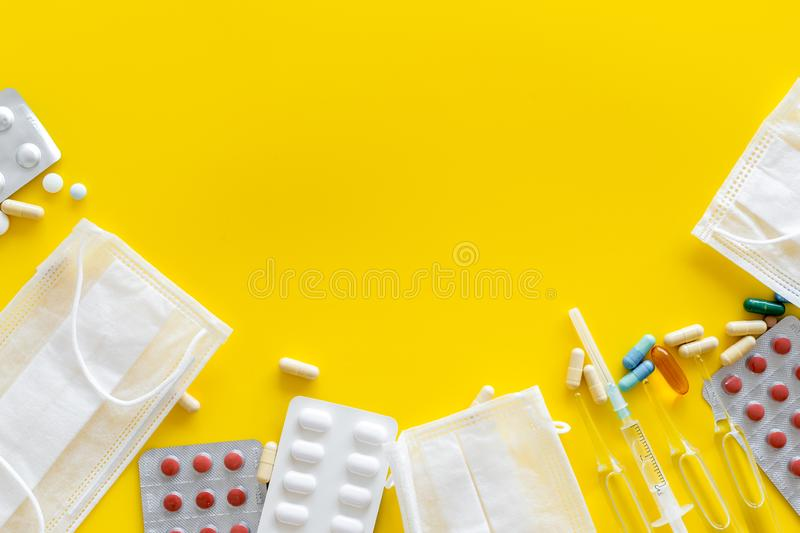 Treat flu and cold concept. Vaccine, mask, pills on yellow background top view frame copy space. Treat flu and cold concept. Vaccine, mask, pills on yellow royalty free stock photo