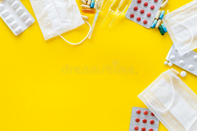 Treat flu and cold concept. Vaccine, mask, pills on yellow background top view frame copy space. Treat flu and cold concept. Vaccine, mask, pills on yellow royalty free stock image