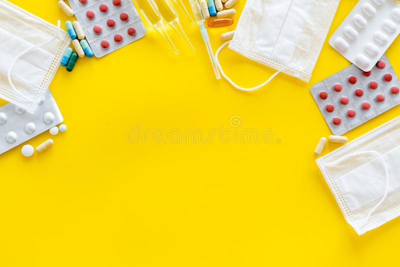 Treat flu and cold concept. Vaccine, mask, pills on yellow background top view frame copy space. Treat flu and cold concept. Vaccine, mask, pills on yellow royalty free stock photography