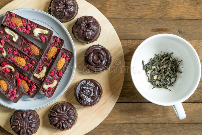 A treat for tea. Close up healthy vegan chocolate dessert with tea cup near. Top view. Delicious homemade sticks and. Candies with raspberries, almonds and royalty free stock photography