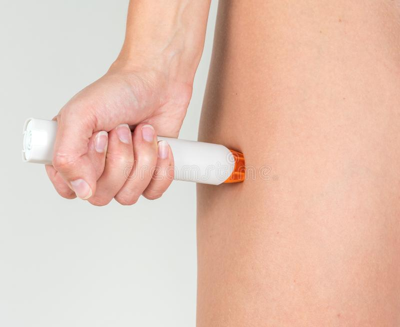 Treating the allergic reaction with the epinephrine. Treating the severe allergic reaction with the epinephrine stock image