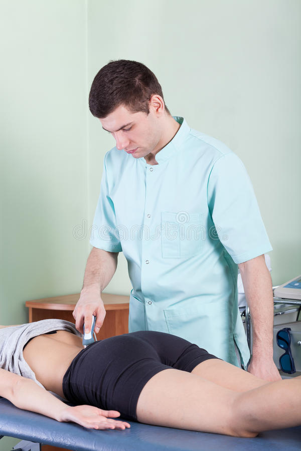 Treatment of back pain by laser therapy stock photo