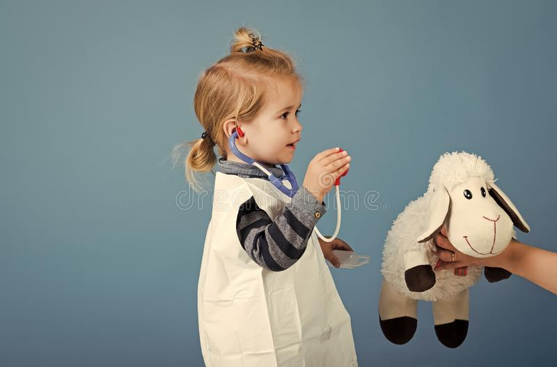 Treatment of children. Boy play veterinarian with toy sheep in mothers hand. Child doctor examine toy pet with stethoscope on blue background. Veterinary royalty free stock image