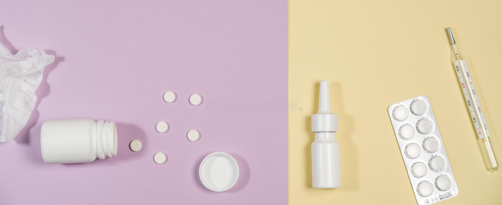 Various medicines, a thermometer, sprays from a stuffy nose and a pain in a throat on a pink background stock photo