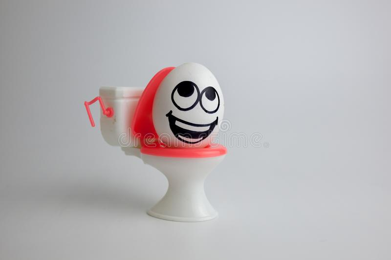 Treatment of constipation concept. Pain in the toilet. A comic egg with a painted face on a toy umbrella stock image