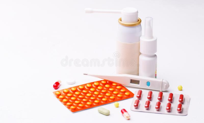 Treatment of flu. Throat spray, nose drops, cold pills and thermometer on white background. Concept helth and medecine royalty free stock images
