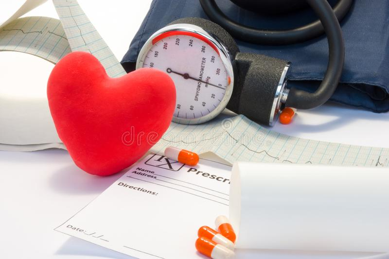 Treatment of heart, hypertension and cardiovascular disease concept photo. Volume model card red heart lies on table near the EKG royalty free stock image
