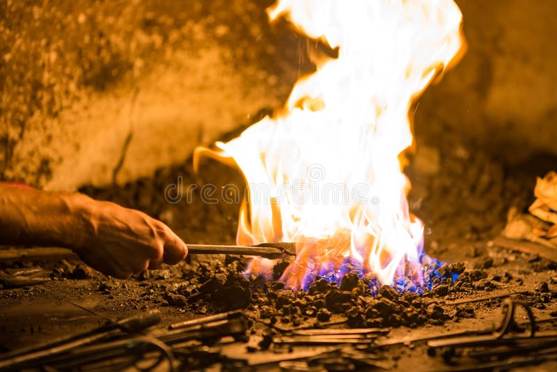 Treatment of molten metal close-up. Handmade blacksmith. In the forge stock images
