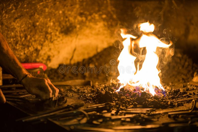 Treatment of molten metal close-up. Handmade blacksmith. In the forge stock photography