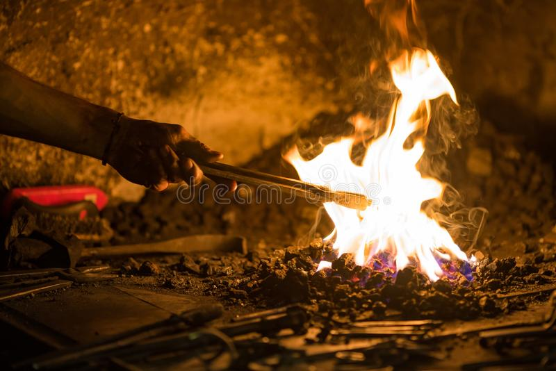 Treatment of molten metal close-up. Handmade blacksmith. In the forge stock photo