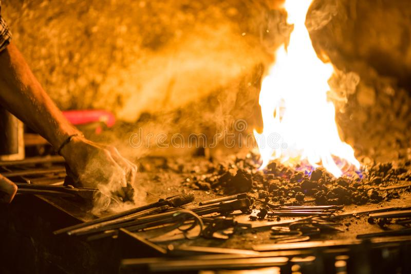 Treatment of molten metal close-up. Handmade blacksmith. In the forge royalty free stock photo