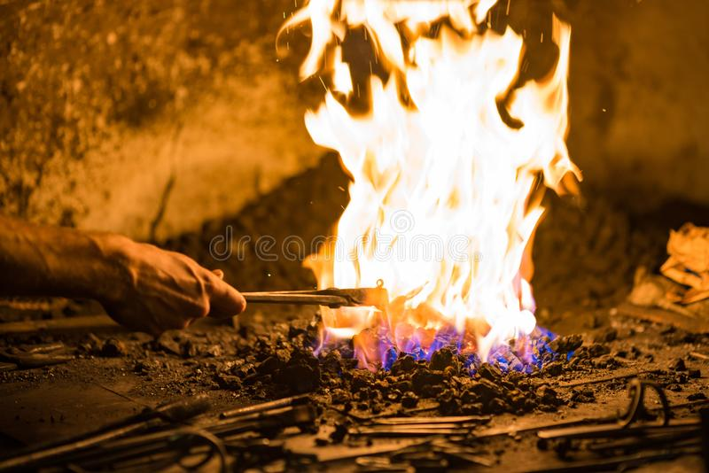 Treatment of molten metal close-up. Handmade blacksmith. In the forge royalty free stock image