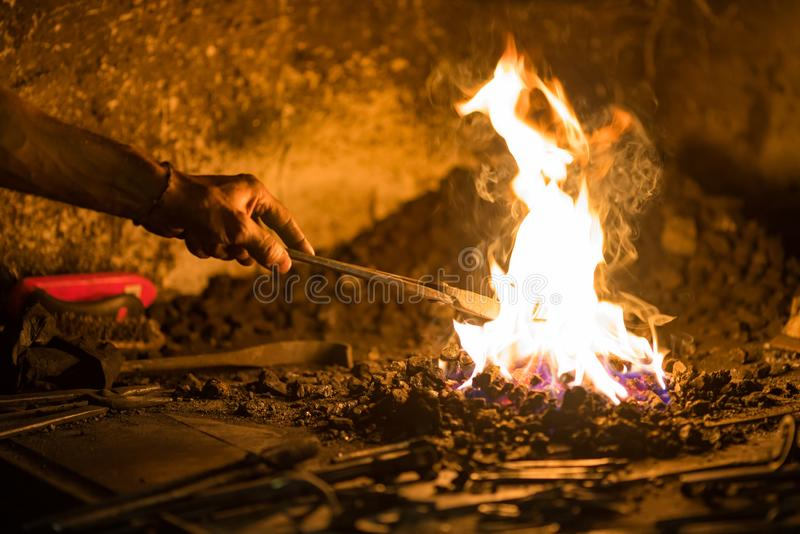 Treatment of molten metal close-up. Handmade blacksmith. In the forge royalty free stock photos