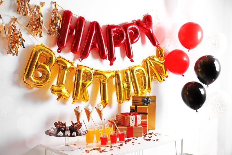 Treats and gifts on table in room decorated for birthday party with balloons stock image