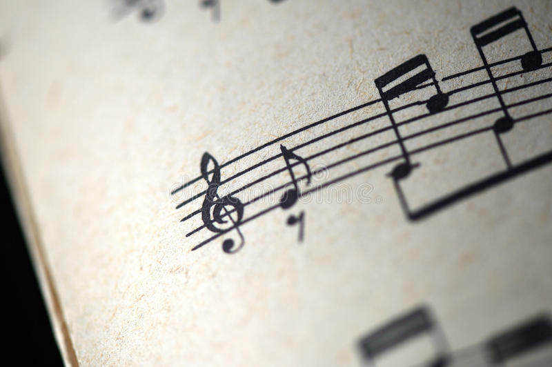 Treble clef and musical notes in the old musical notebook. Close up stock image