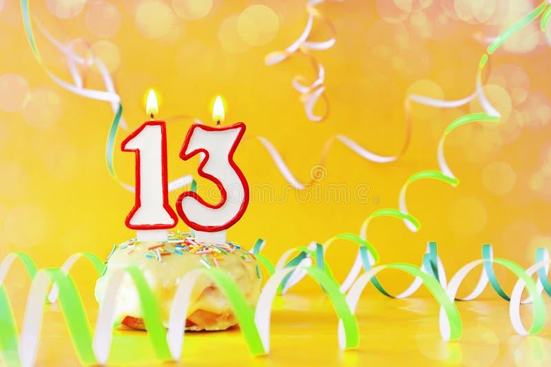 Trece años de cumpleaños Magdalena con las velas ardientes bajo la forma de número 13 fotografía de archivo