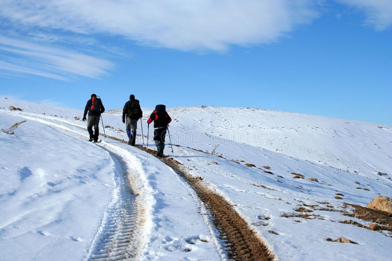 Trecking auf schneebedecktem Pfad an einem sonnigen Wintertag lizenzfreie stockbilder