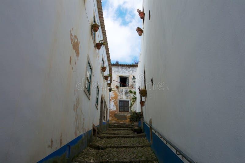 Treden in een lege straat met witte oude huizen stock foto's