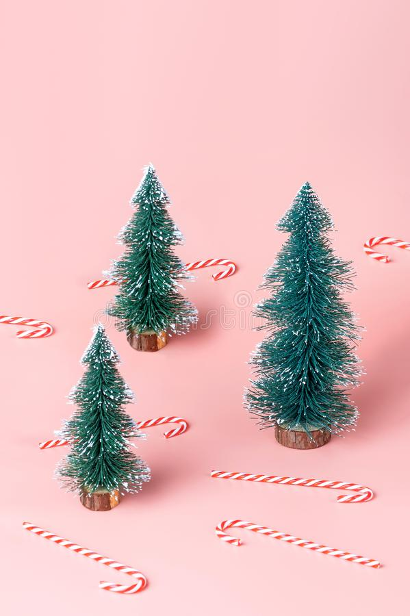 Tree Christmas tree with candy cane on pastel pink studio background.Holiday festive celebration greeting card with copy space. royalty free stock photos
