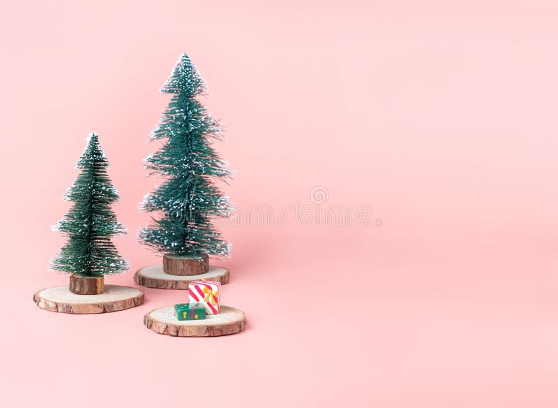 Tree Christmas tree on wood log slice with present box on pastel stock photo
