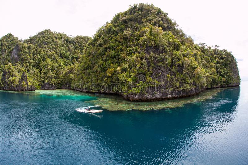 Tree-Covered Limestone Islands in Raja Ampat. Rugged limestone islands are found in Raja Ampat, Indonesia. This remote, tropical region is home to an array of stock photography